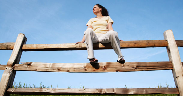 Woman sitting on a fence