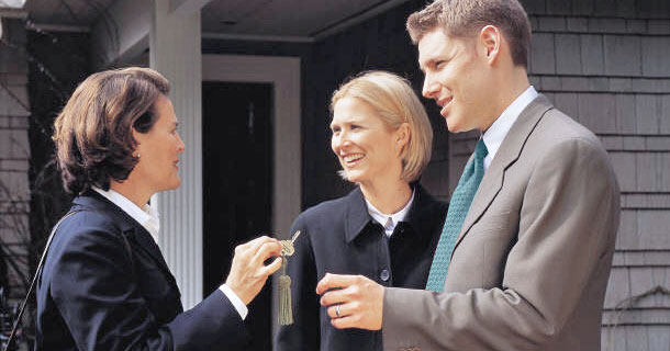 Real estate agent handing keys to her clients
