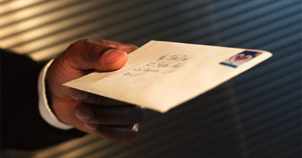 man holding mailed envelope