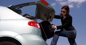 woman removing bag from car trunk